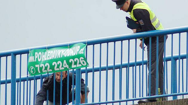 Policisté měří výšku z nadchodu nad silnicí I/13, odkud spadl mladý muž.