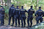 Kriminalisté ohledávají okolí domu, kde k tragédii došlo.