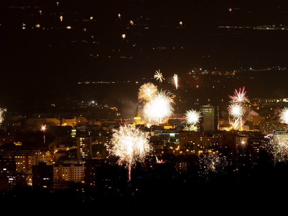 Pohled z hor na město Chomutov, které vítá mnoha ohňostroji příchod nového roku.