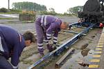 Zaměstnanci přepravní společnosti museli s kamionem najet na trať a z návěsu vyklopit speciální koleje, po kterých se stařičká lokomotiva III A Donnersberg mohla pomaličku spustit  dolů.