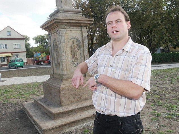 Zprvu asfaltová poušť, nyní malebná náves se sochou patrona. Na snímku starosta Luděk Pěnkava.