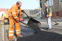 Dělníci opravují v chomutovské ulici Na Příkopech výtluky na poničené vozovce.