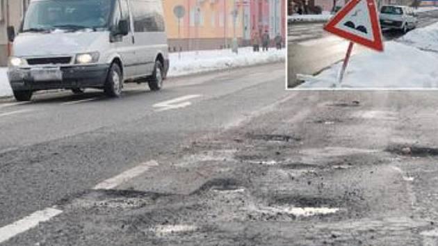 SAMÁ DÍRA. Děravá Mostecká ulice, část od křižovatky pod gymnáziem směrem k centru města. Díry i značka, která na ně upozorňuje (vložený snímek), tu zřejmě zůstanou až do jara.