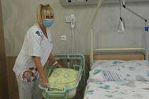 Staniční sestra představuje nadstandartní pokoj. Maminka má novorozence v těsné blízkosti.