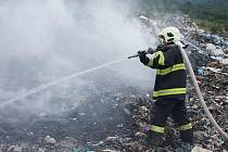 Hasič kropí odpadky, které vzplály na skládce u Vysoké Pece.