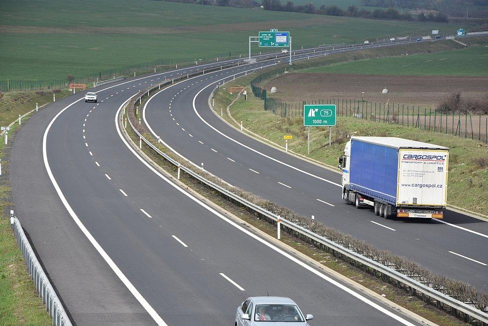 Mezi vesnicí a lesíkem vede dálnice D7.