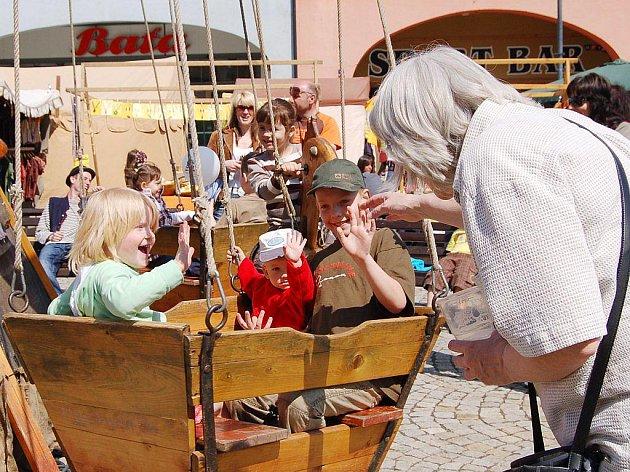 Děti se na dřevěném kolotoči uprostřed náměstí pořádně bavily.