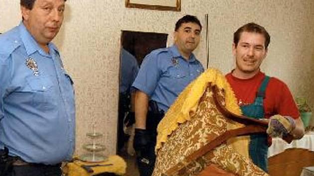 EXEKUCE. Pomocníci exekutora vynášejí za asistence strážníků z bytu dlužníka všechny věci. Neplatič musel byt opustit v doprovodu městské policie a se dvěma igelitkami