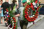 Jeden z vojáků nese věnce do kostela svatého Ignáce, kde se koná pohřeb Davida Beneše.