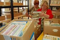 SCI–FI, BÁSNĚ, ROMÁNY... Knihovnice Eva Martinovcová (vepředu) a dobrovolnice Milada Švingrová vykládají knihy z krabic do regálů v nové knihovně. Otevře v červnu.