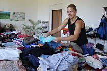 VEŘEJNÁ SKŘÍŇ. Anežka Ješinová ze spolku Setkávání - živý venkov přerovnává hromádky s oblečením. Lidé je mohou nosit zdarma a s sebou si vybrat brát jiné oblečení. Stojí to jen dvacku.