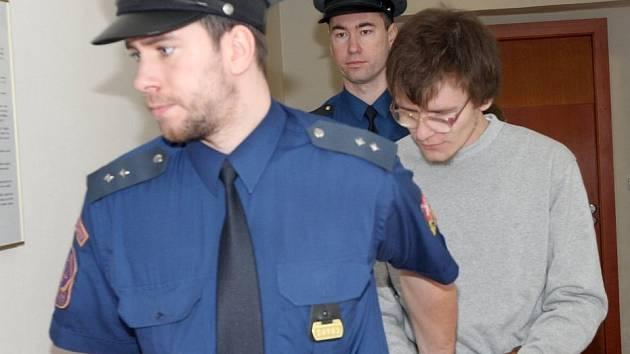 Vězeňská stráž přivádí do jednací síně chomutovského soudu třicetiletého Ladislava B. obžaslovaného z pohlavního zneužívání teprve třináctiletého školáka.