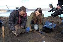 Archeologové Kryštof Derner a Věra Sušická vyzvedávají poslední kosterní pozůstatky za pozornosti televizních štábů a novinářů.