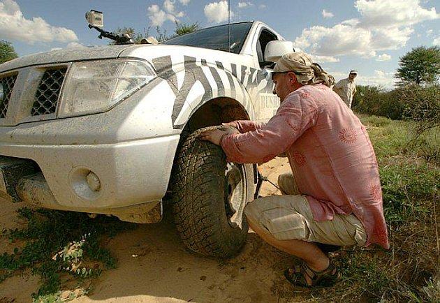 Měníme kolo uprostřed Kalahari. Buš kolem je poměrně hustý. Jsme ostražití, protože lehkovážnost se nevyplácí.