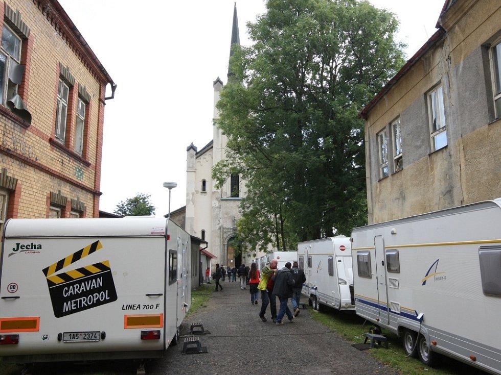 Přístup ke kostelu lemují karavany se zázemím filmařského štábu.