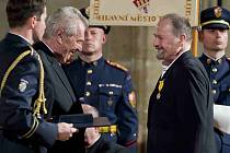 PREZIDENT A BÁSNÍK. Miloš Zeman předává Jiřímu Žáčkovi státní vyznamenání. Básník, který strávil své rané dětství na Chomutovsku, obdržel medaili za zásluhy o stát v oblasti umění.