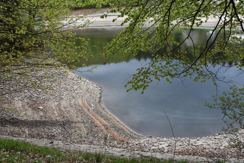 Břehy přehrady se s ustupující hladinou víc a víc odhalují.