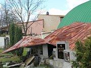 Střecha ze školní tělocvičny ve Strupčicích (na snímku světlá stavba uprostřed) se složila pod hřbitovní zdí.