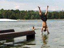 BANDA TÁHNE. Stále více lidé tráví svůj čas v parných dnech u Velkého otvického rybníka. V odpoledních hodinách je okolí Bandy zcela obloženo opalujícími se lidmi, někteří se nebojí vydat ani do vody.