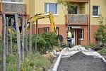 Před bytovými domy v Březně, kde se rozkládá parčík s vinohradem, právě pracují na novém chodníku.