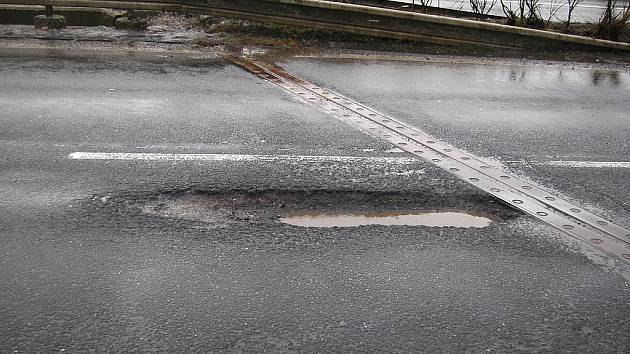 Díra na silnici mezi Chomutovem a Mostem