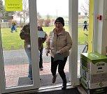 První údlická volička Marie Albrechtová - do dveří ji pouští Údličan, který na otevření volební síně čekal téměř čtvrt hodiny.