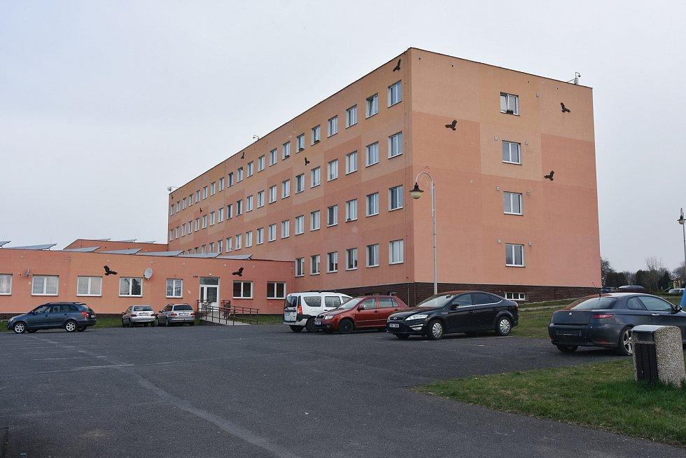 Bytový dům vznikl přestavbou bývalých kasáren v Hrušovanech. Místní lidé mají k využití i parkoviště, sportovní a dětské hřiště či zahrádky. Také bytovky mají na střeše solární panely.