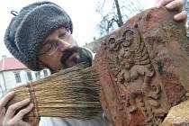 Archeologický technik Kryštof Derner čistí jeden z nalezených keramických ozdobných článků terakotu, který archeologové vykopali na chomutovkém Žižkově náměstí.