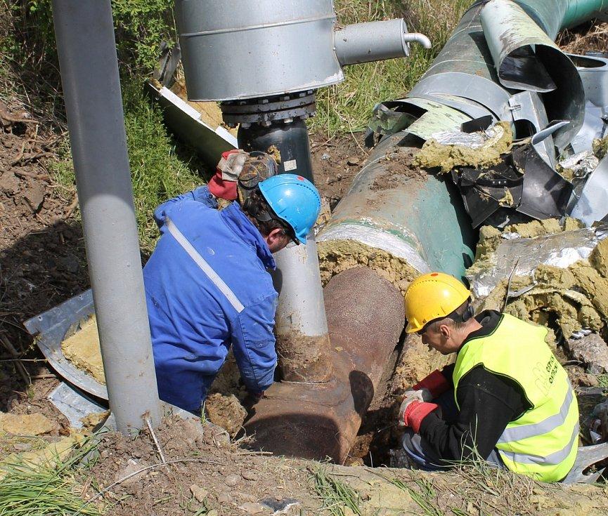 Zaměstnanci Mostecká montážní, a. s., obhlížejí místo poškození přípojky ve velkém potrubí. Přípojka vede na Průmyslovou zónu Verne.