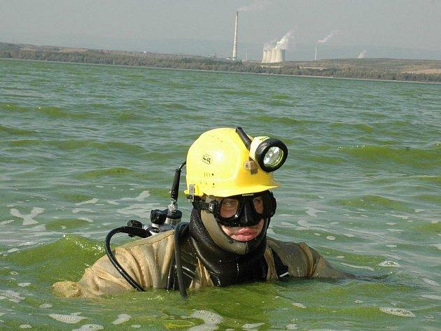 Potápěč Jan Bečkovský ve vodě Nechranic při opravě hráze přehrady. V pozadí Elektrárna Tušimice.