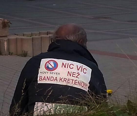 fotografie bezdomovce, který měl na zádech nášivku nadávající členům hnutí Nový Sever.