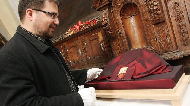 OSTATKY ukryté v malé schránce nechali muzejníci ovinout látkou tak, jak se to dělávalo za starých časů, kdy se balily do vzácných textílií. Kvůli klimatu jsou schovány pod skleněným poklopem. Na snímku kadaňský historik Lukáš Gavenda.
