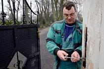Pan Miroslav Duchek při opravě vrat hlavního městského hřbitova.