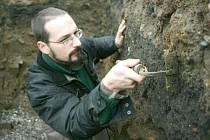 Technik Kryštof Derner si prohlíží nalezený střep na chomutovském Žižkově náměstí, které nyní obsadili archeologové z Ústavu archeologické a památkové péče v Mostě.