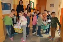 Děti udělají radost jiným vrstevníkům krabicemi naplněnými dárky.