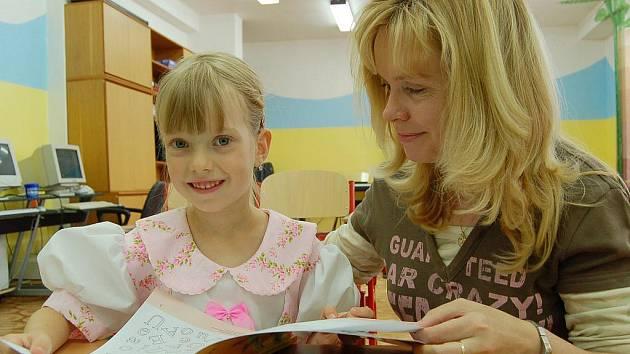 Malá školačka Lucie Svitáková už je natěšená, až začne školy. Do své třídy se přišla podívat o dva dny dříve a vzala si na to sváteční šaty. Spolu s ředitelkou školy Petrou Jandovou (na snímku) si prošly nové učebnice.