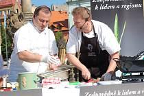 """Přímo na náměstí se otevřela""""farmářská"""" kuchyně. Kuchař Michal """"Sam"""" Horák (vpravo) ukázal všem návštěvníkům trhů, jak rychle lze uvařit nedělní oběd z produktů, které právě zakoupili."""
