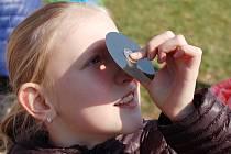 Dívka před ZŠ Duhová cesta sleduje zatmění Slunce skrz magnetický kotouč z diskety.