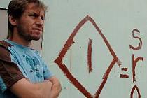 PONIČENÁ FASÁDA. Milan Novák stojí před domem své rodiny, který byl pomalován. Další nápisy byly Gumo!, STB a jiné.