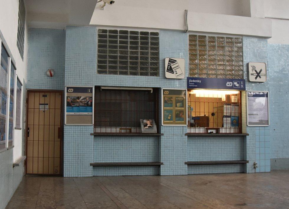 Vestibul železniční zastávky Jirkov působí opuštěně. Dojem umocňují zamřížované dveře a okna včetně výdejních.