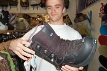Prodavač v chomutovském skate shopu KOule Láďa Telenský předvádí, jaké boty na snowboard by si lidé měli koupit. Šetřit se prý na nich nedá.