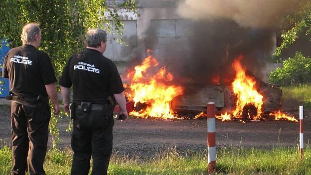Auto v plamenech - přihlížejí jirkovští strážníci, kteří byli na místě první.