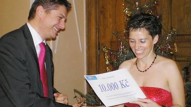 František Jochman z Asistenčního centra Most předal primářce dětského oddělení kadaňské nemocnice Patricii Kotalíkové šek na deseti tisíc korun.