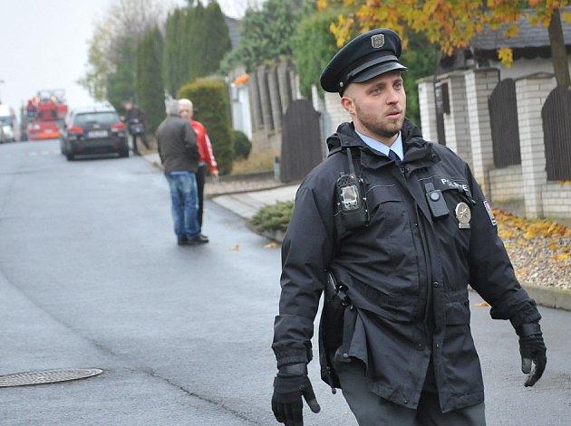 Policista hlídá na místě vyšetřování.