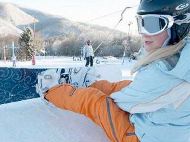 Mladá snowboardistka na svahu sjezdovky v Klínech na Mostecku. O víkendu byly hory plné.