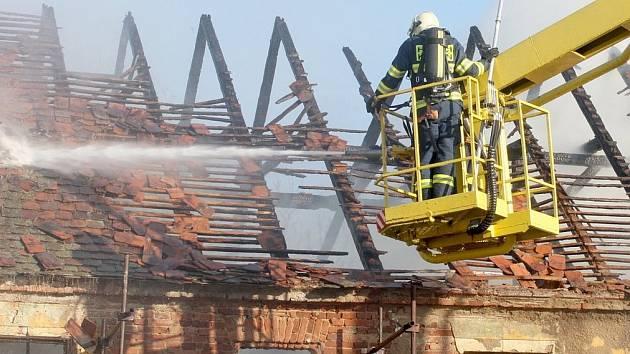 Hasiči kropí požárem zničenou střechu.