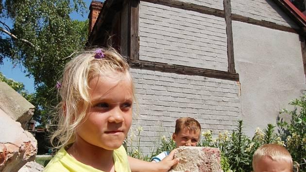 ŠKOLKA. Do mateřské školky ve Spořicích se vejde více dětí. Na místě dnešního přístavku postaví další budovu, která bude se školkou propojena. Děti (na snímku vlevo Martina Fritschová ) se už těší na nové učebny. Zatím si jen prohlížejí kusy zbouraného za