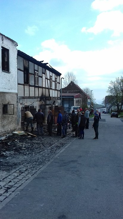 Na snímku je zástup lidí, kteří přišli po požáru pomoct s likvidací následků.