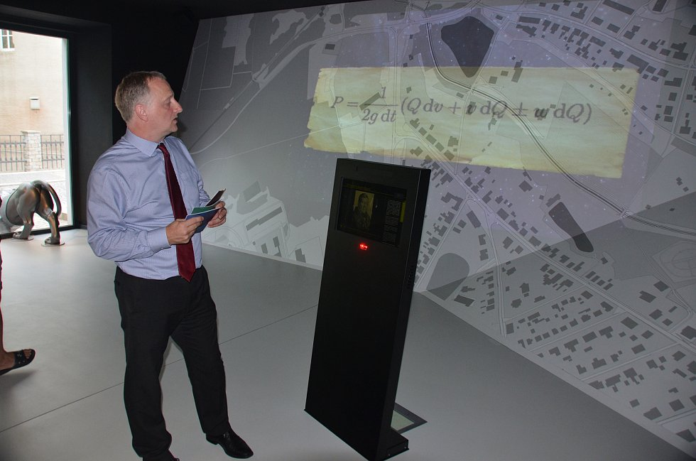 V Jirkově otevřeli nové infocentrum s multimediálním hasičským muzeem. Projektový specialista Jan Buriánek ukazuje část věnovanou historii města.