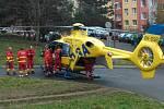 Záchranáři nakládají těžce zraněného muže do vrtulníku.